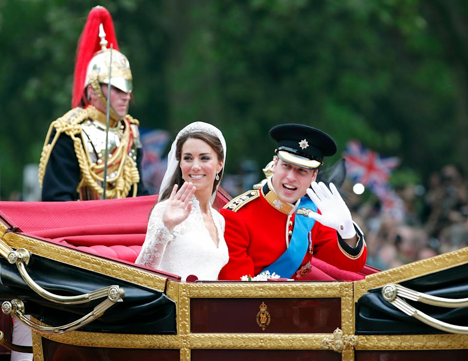 Catherine, Duchess of Cambridge and Prince William, Duke of Cambridge (wearing his red tunic uniform of the Irish Guards, of which he is Colonel) travel down The Mall, on route to Buckingham Palace, in the 1902 State Landau horse drawn carriage following their wedding ceremony at Westminster Abbey on April 29, 2011 in London, England