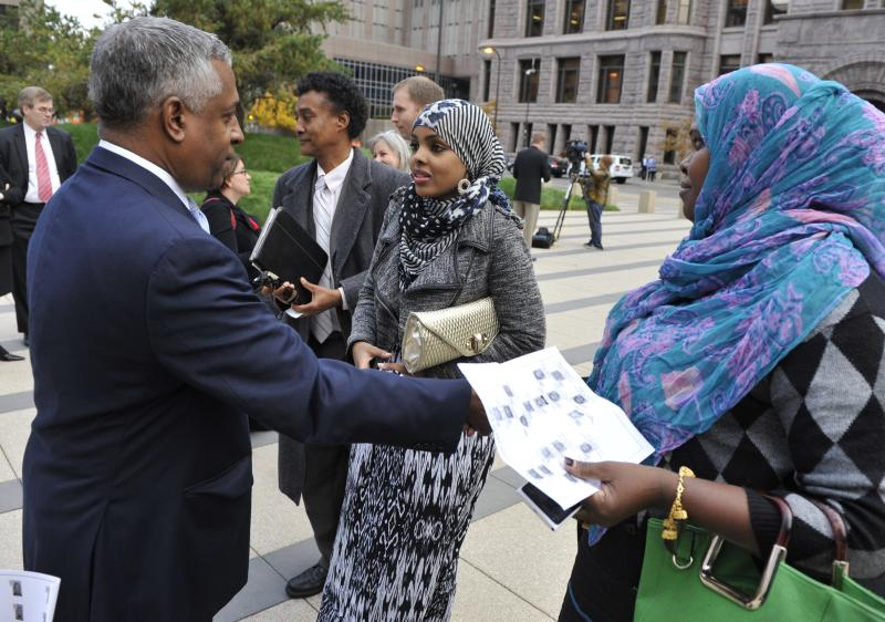 Istar Abdi, right, a member of the Minneapolis Somali community, right, shakes hands with U.S. Attorney B.Todd Jones, left, after a federal jury in Minneapolis on Thursday, Oct. 18, 2012 convicted Mahamud Said Omar on all five terrorism-related charges of helping send young men through a terrorist pipeline from Minnesota to Somalia. Abdi, a mom, said she attended the sentencing to get feedback and to hear the jury's verdict. In center is Amal Ibrahim, a Somali interpreter for the trial. (AP Photo/Jim Mone)