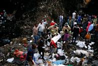 Rescue workers carry the body of a victim recovered out from a pile of garbage following a landslide when a mound of trash collapsed on an informal settlement at the Koshe garbage dump in Ethiopia's capital Addis Ababa, March 13, 2017. REUTERS/Tiksa Negeri