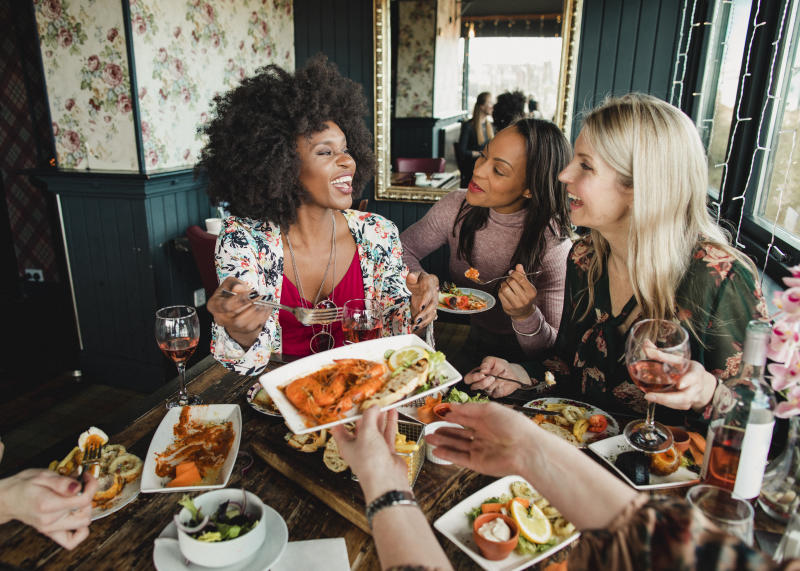 A group of women are enjoying a meal in a restaurant with rose wine. They have prawns and a sharing platter with them, one woman can be seen passing her friend a plate of food.