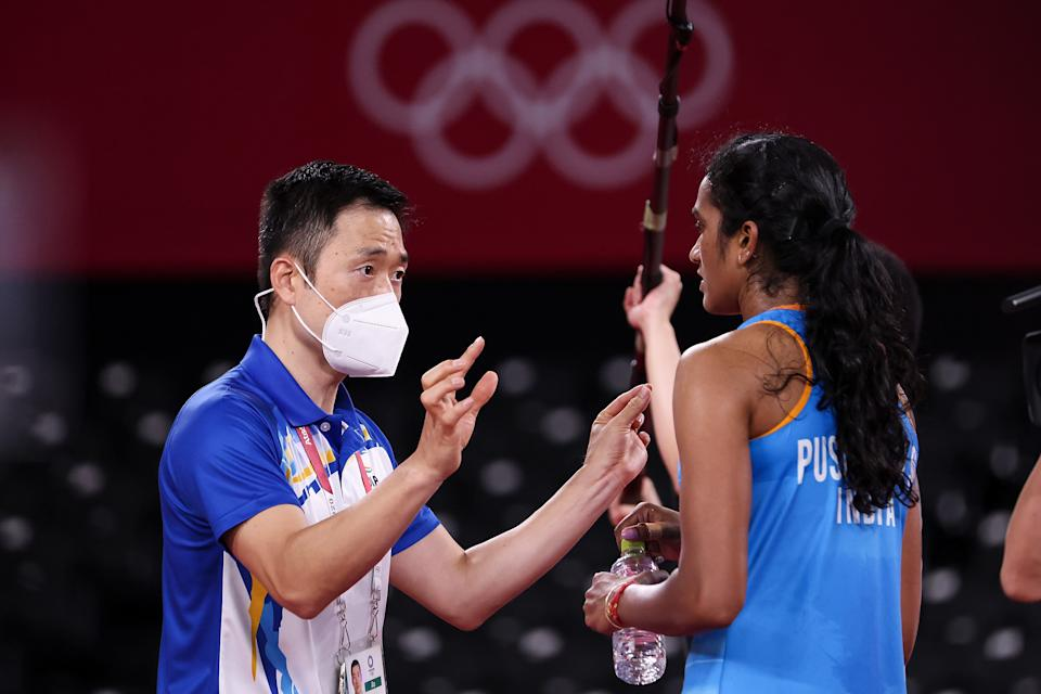 CHOFU, JAPAN - AUGUST 01: Pusarla V. Sindhu of Team India talks to her coach Park Tae-sang(left) as she competes against He Bing Jiao of Team China during the Women's Singles Bronze Medal match on day nine of the Tokyo 2020 Olympic Games at Musashino Forest Sport Plaza on August 01, 2021 in Chofu, Tokyo, Japan. (Photo by Lintao Zhang/Getty Images)