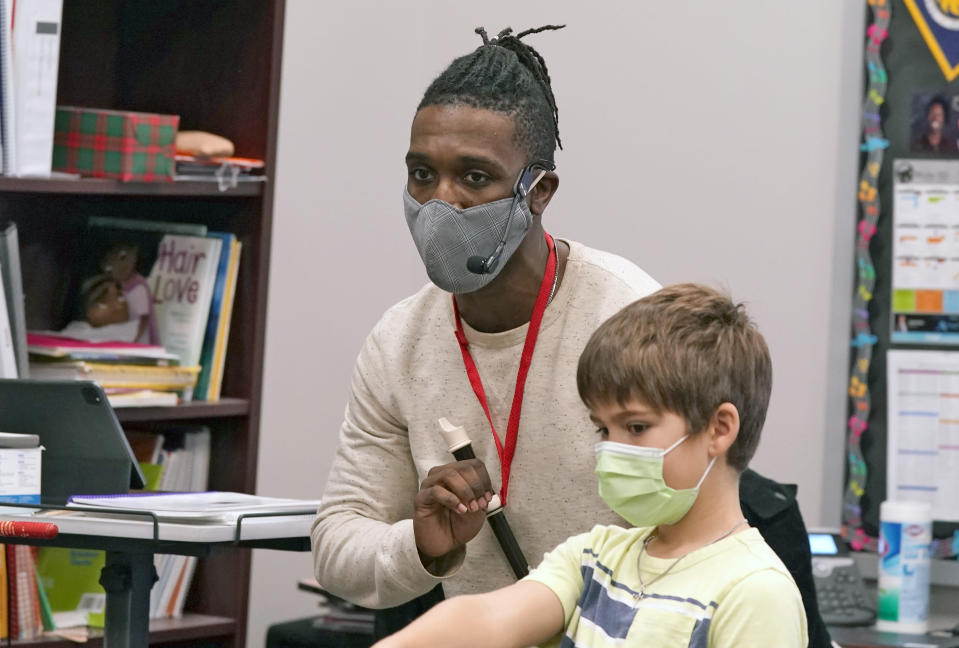 Elementary school music teacher Jami Brown, left, uses a mic to work with his class including third grader Walker Moore at Tibbals Elementary School in Murphy, Texas, Thursday, Dec. 3, 2020. Texas Gov. Greg Abbot's statewide mask order does not mandate face covering for children under the age of 10, allowing some school districts to not require masks for children leaving the choice of mask use up to the parents. (AP Photo/LM Otero)