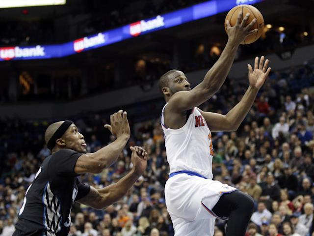 New York Knicks' Raymond Felton, right, lays up a shot as Minnesota Timberwolves' Dante Cunningham looks on in the second half of an NBA basketball game, Wednesday, March 5, 2014, in Minneapolis. The Knicks won 118-106. Felton scored 18 points. (AP Photo/Jim Mone)