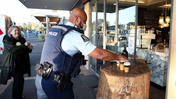 PHOTO: A police officer wearing a mask gets his morning coffee from The Store in Kohimarama as Auckland wakes to a return to level three lockdown, Aug. 13, 2020, in Auckland, New Zealand. (Fiona Goodall/Getty Images)