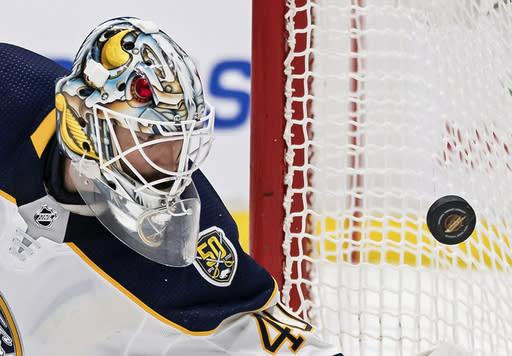 Buffalo Sabres goalie Carter Hutton watches the puck bounce off the side of the net during the second period of an NHL hockey game against the Vancouver Canucks, Saturday, Dec. 7, 2019, in Vancouver, British Columbia. (Darryl Dyck/The Canadian Press via AP)