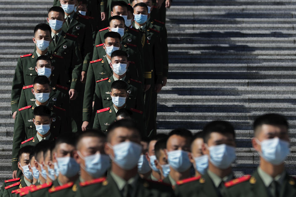 Chinese paramilitary policemen wearing face masks to help curb the spread of the coronavirus march down a staircase outside the Great Hall of the People after attending the commemorating conference on the 70th anniversary of China's entry into the 1950-53 Korean War, in Beijing Friday, Oct. 23, 2020. (AP Photo/Andy Wong)