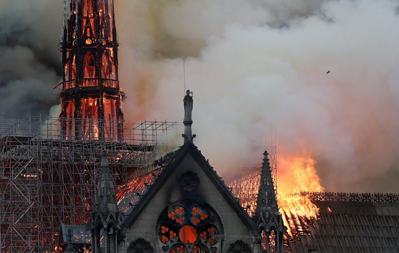 Smoke billows near scaffolding as fire engulfs the spire of Notre Dame Cathedral in Paris, France April 15, 2019. REUTERS/Benoit Tessier
