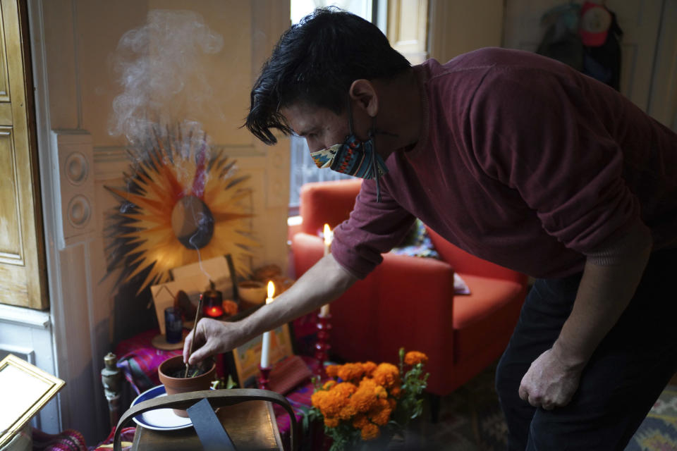 "Sebastian Diaz Aguirre places incense in a Day of the Dead altar dedicated to his father, who died in a nursing home in Mexico last month, Wednesday , Oct. 28, 2020 in the Brooklyn borough of New York ""It feels extremely comforting. I do feel I have a connection with my dad,"" said Diaz Aguirre, who set up his first ofrenda, or altar, since moving to the U.S. eight years ago. (AP Photo/Emily Leshner)"