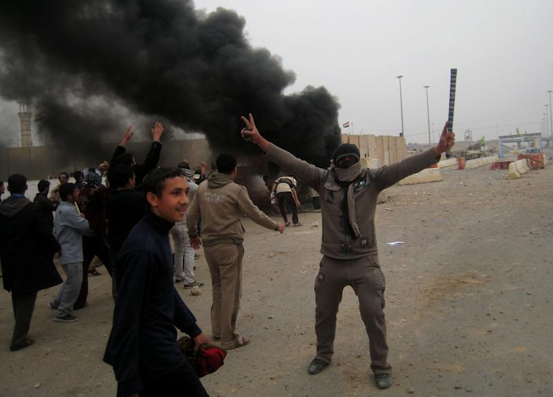 Protesters chant slogans against Iraq's Shiite-led government next to burning an Iraqi army armored vehicle during clashes in Fallujah, 40 miles (65 kilometers) west of Baghdad, Iraq, Friday, Jan. 25, 2013. Iraqi troops shot dead five protesters Friday as they opened fire at stone-hurling demonstrators angry at the troops for preventing them from joining an anti-government rally west of Baghdad, officials said. (AP Photo/ Bilal Fawzi)