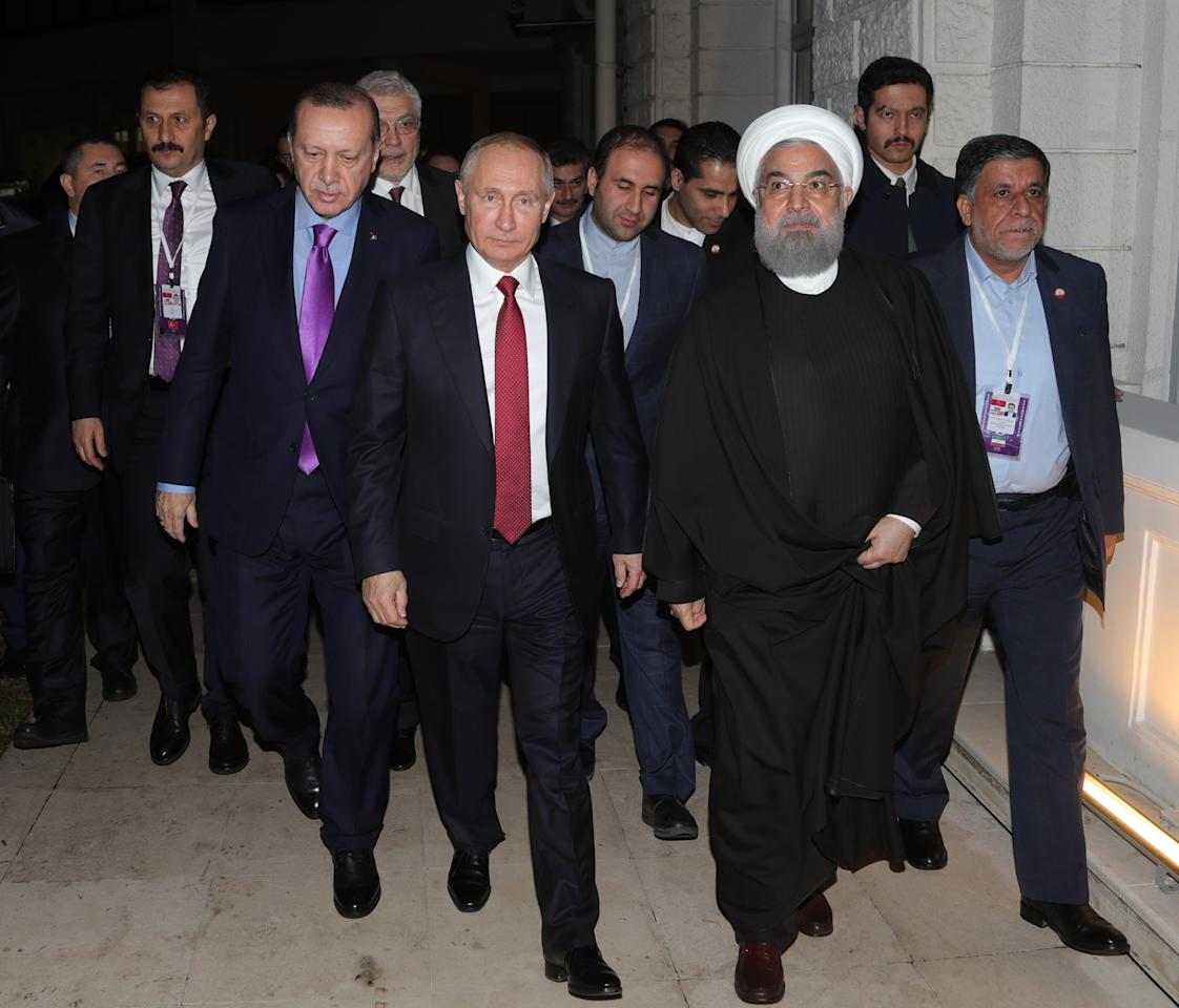 Turkey's President Recep Tayyip Erdogan, 2nd right, Russia's President Vladimir Putin, center, and Iran's President Hassan Rouhani walk after a news conference in Russia's Black Sea resort of Sochi, Russia, Wednesday, Nov. 22, 2017. The presidents of Turkey and Iran have hailed their trilateral talks with Russia on Syria's future as critical for restoring peace in the war-torn nation. (Mikhail Klimentyev/Pool Photo via AP)