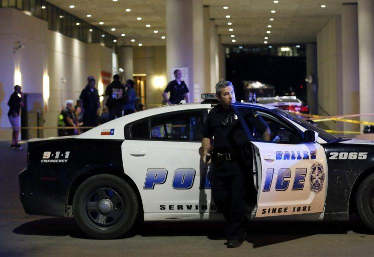 A Dallas police officer steps out of a vehicle as he arrives in front of Baylor University Medical Center where several others were police were already gathered, Friday, July 8, 2016, in Dallas. (AP Photo/Tony Gutierrez)