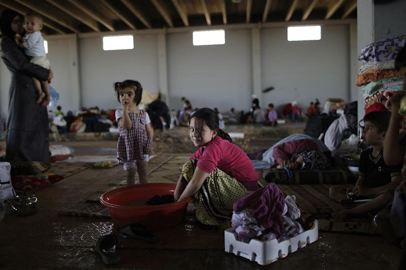 Syrian girl, wa'd Ismael, 8. bottom center, who fled her home with her family in Marea 11 days ago, due to Syrian government shelling in their neighborhood, washes her family's laundry in a tub, as she and others take refuge at the Bab Al-Salameh border crossing, in hopes of entering one of the refugee camps in Turkey, near the Syrian town of Azaz, Monday, Sept. 3, 2012. (AP Photo/Muhammed Muheisen)