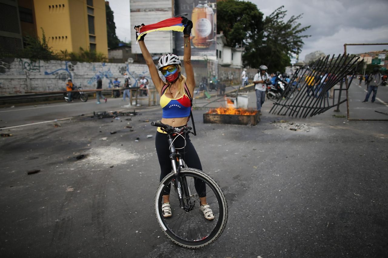 <p>A demonstrator astride her bicycle with her face painted in the Venezuelan national colors, holds a Venezuelan flag during a national sit-in against President Nicolas Maduro, in Caracas, Venezuela, Monday, May 15, 2017. (AP Photo/Ariana Cubillos) </p>