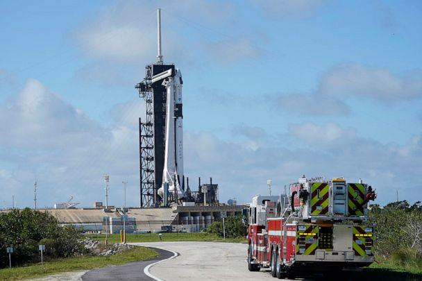 PHOTO: NASA firefighters drive on the road outside the fence near a SpaceX Falcon 9 rocket sits on the launch pad at  at the Kennedy Space Center in Cape Canaveral, Fla., Nov. 13. 2020. (Chris O'meara/AP)