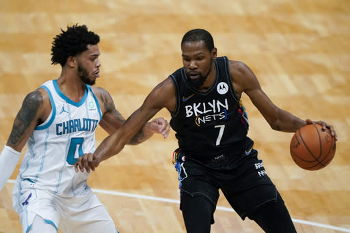 Brooklyn Nets forward Kevin Durant drives around Charlotte Hornets forward Miles Bridges during the first half of an NBA basketball game in Charlotte, N.C., Sunday, Dec. 27, 2020. (AP Photo/Chris Carlson)