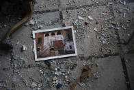A photo rests among broken glass on the floor of the Sursock Palace, heavily damaged after the explosion in the seaport of Beirut, Lebanon, Friday, Aug. 7, 2020. The Sursock palace, built in 1860 in the heart of historical Beirut on top of a hill overlooking the now-obliterated port, is home to beautiful works of arts, Ottoman-era furniture, marble and paintings from Italy — the result of more than three long-lasting generations of the Sursock family. (AP Photo/Felipe Dana)