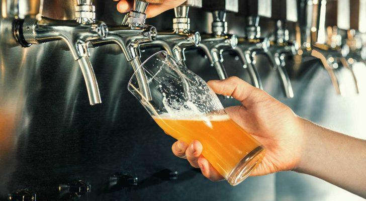 A photo of a person pouring a beer from a tap.