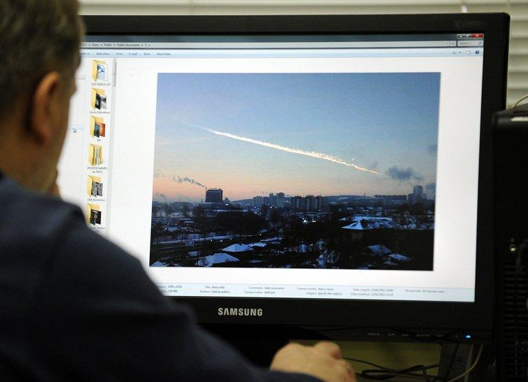 A man in Moscow looks at a computer screen displaying a picture reportedly taken in the city of Chelyabinsk, on February 15, 2013, showing the trail of a falling object above a residential area of the city