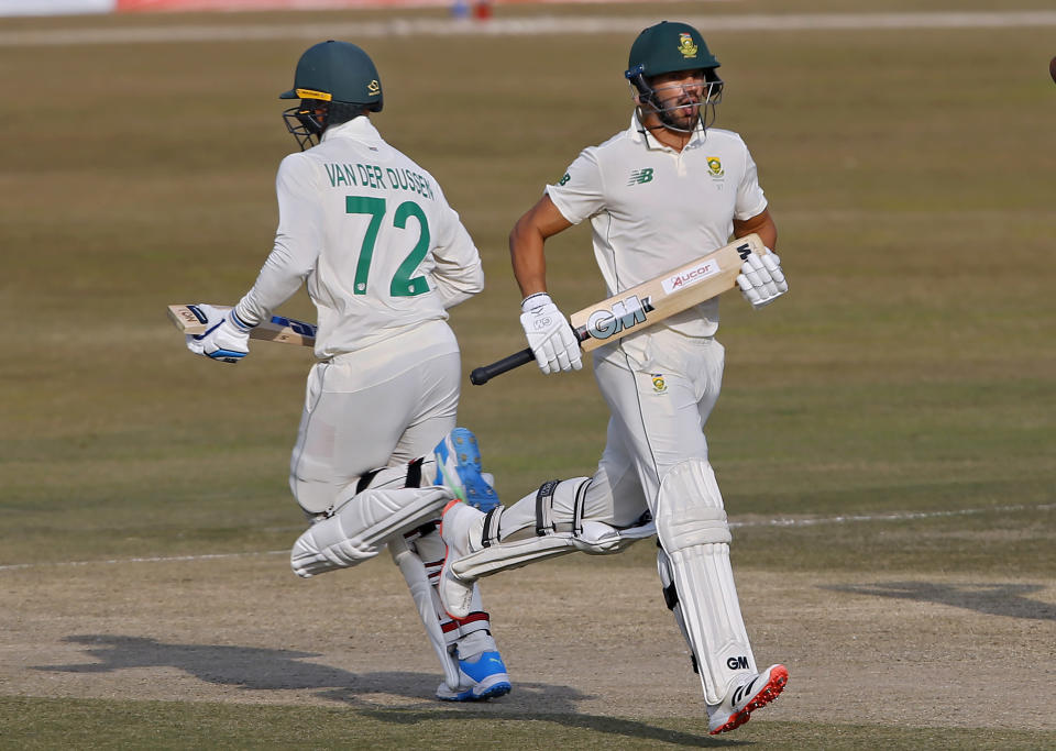 South Africa's Aiden Markram, right, and Rassie van der Dussen run between the wickets during the fourth day of the second cricket test match between Pakistan and South Africa at the Pindi Stadium in Rawalpindi, Pakistan, Sunday, Feb. 7, 2021. (AP Photo/Anjum Naveed)