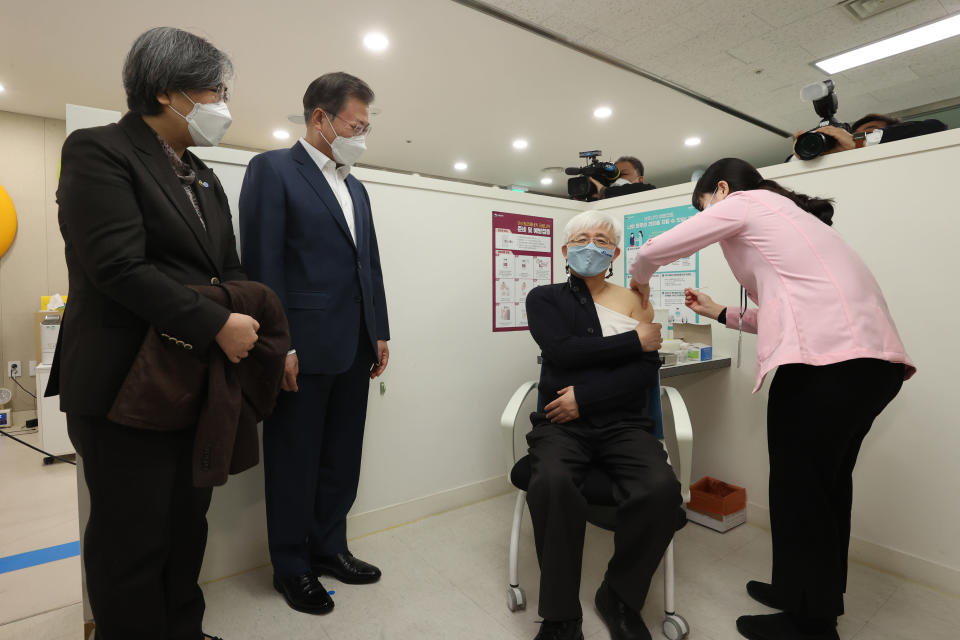 South Korean President Moon Jae-in, second from left, watches a doctor receives a shot of AstraZeneca vaccine at a public health center in Seoul, South Korea, Friday, Feb. 26, 2021. South Korea on Friday administered its first available shots of coronavirus vaccines to people at long-term care facilities, launching a mass immunization campaign that health authorities hope will restore some level of normalcy by the end of the year.(Choe Jae-koo/Yonhap via AP)