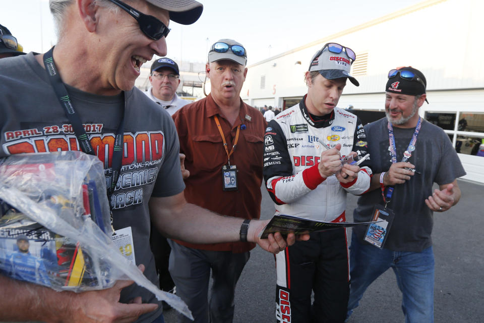Brad Keselowski, second from right, gives autographs after winning the pole for a NASCAR Monster Energy Cup auto race at Richmond Raceway in Richmond, Va., Friday, Sept. 20, 2019. (AP Photo/Steve Helber)