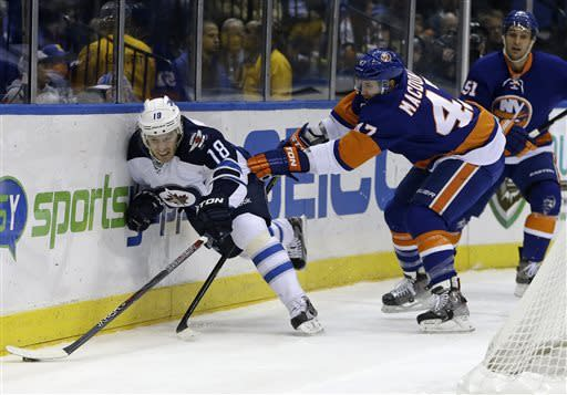 New York Islanders defenseman Andrew MacDonald (47) tries to stop Winnipeg Jets center Bryan Little (18) from getting to the puck in the first period of their NHL hockey game at Nassau Coliseum in Uniondale, N.Y., Tuesday, April 2, 2013. (AP Photo/Kathy Willens)