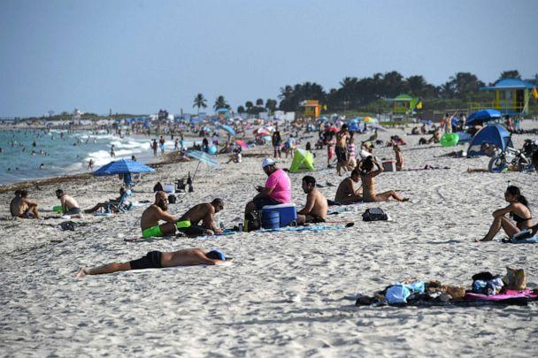PHOTO: People are seen on Miami Beach, as Miami Dade County is mandating a daily 8 p.m. to 6 a.m. curfew, July 28, 2020. (Larry Marano/Rex via Shutterstock)