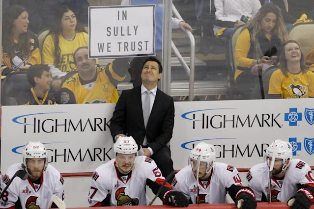 <p>Ottawa Senators head coach Guy Boucher looks up at the scoreboard as a Pittsburgh Penguins fan holds up a sign for Penguins head coach Mike Sullivan during the first period of Game 5 in the NHL hockey Stanley Cup Eastern Conference finals, Sunday, May 21, 2017, in Pittsburgh. (AP Photo/Gene J.Puskar) </p>