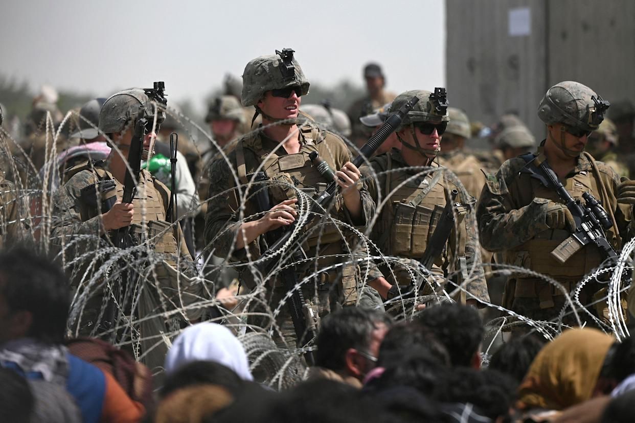 TOPSHOT - US soldiers stand guard behind barbed wire as Afghans sit on a roadside near the military part of the airport in Kabul on August 20, 2021, hoping to flee from the country after the Taliban's military takeover of Afghanistan. (Photo by Wakil KOHSAR / AFP) (Photo by WAKIL KOHSAR/AFP via Getty Images)