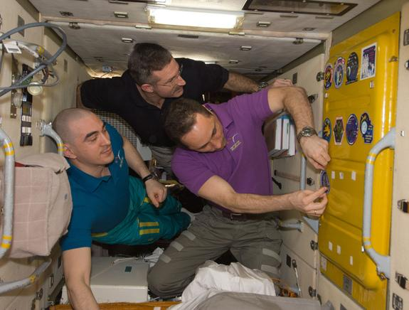 Aboard the International Space Station, NASA astronaut and Expedition 30 commander Dan Burbank (center) and Russian cosmonauts Anton Shkaplerov (right) and Anatoly Ivanishin add the Soyuz TMA-22 patch to the growing collection of insignias repr