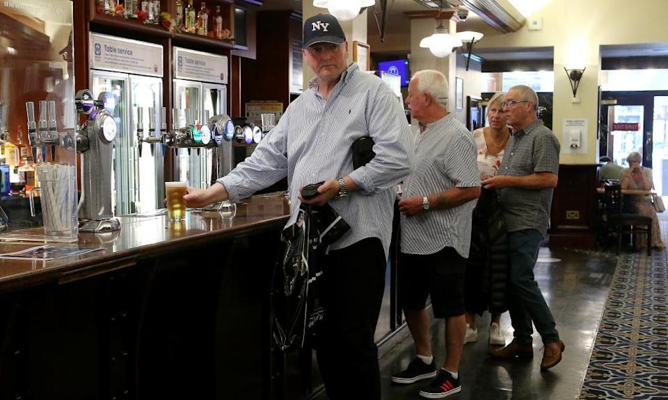 Middle-aged adults in a Manchester pub wait at the bar to be served last week after the lifting of Covid restrictions.