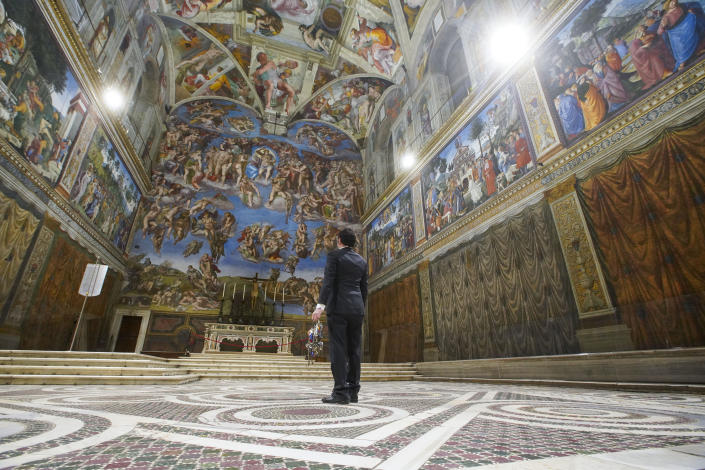 """Gianni Crea, the Vatican Museums chief """"Clavigero"""" key-keeper, walks through the Sistine Chapel as he opens the museum, at the Vatican, Monday, Feb. 1, 2021. Crea is the """"clavigero"""" of the Vatican Museums, the chief key-keeper whose job begins each morning at 5 a.m., opening the doors and turning on the lights through 7 kilometers of one of the world's greatest collections of art and antiquities. The Associated Press followed Crea on his rounds the first day the museum reopened to the public, joining him in the underground """"bunker"""" where the 2,797 keys to the Vatican treasures are kept in wall safes overnight. (AP Photo/Andrew Medichini)"""