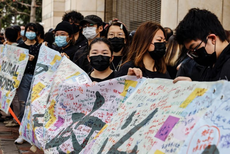 Supporters of pro-democracy activists hold a banner as they queue up for a court hearing over national security law outside West Kowloon Magistrates' Courts, in Hong Kong