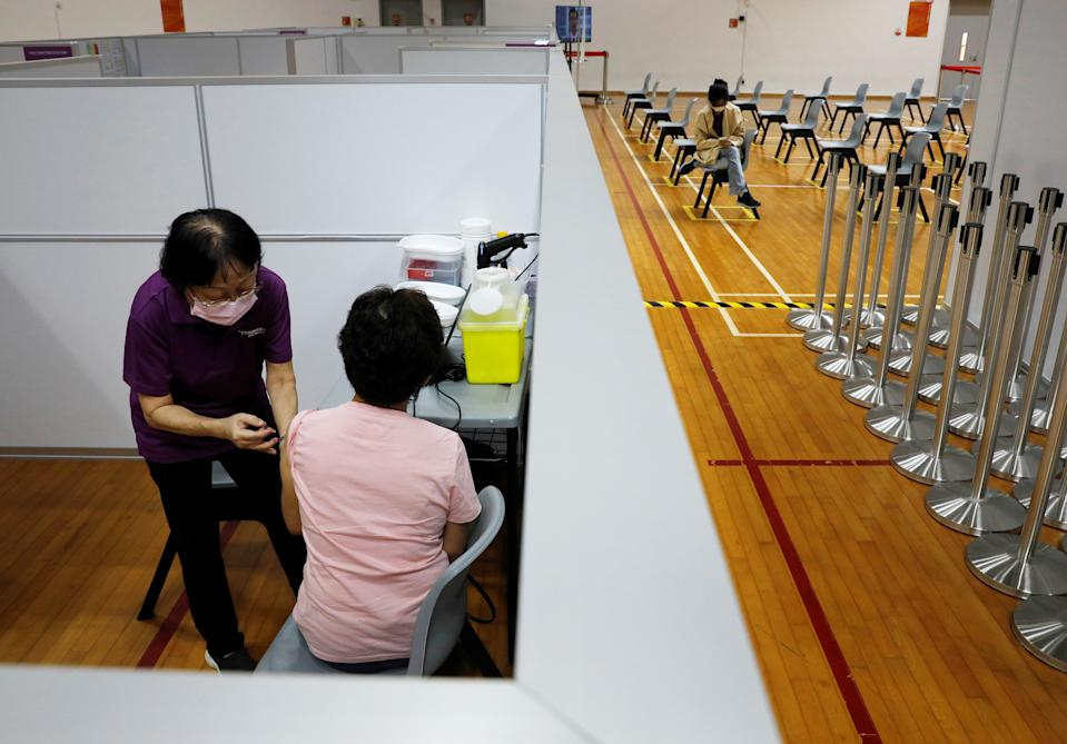 A woman receives her vaccination at a COVID-19 vaccination centre in Singapore.