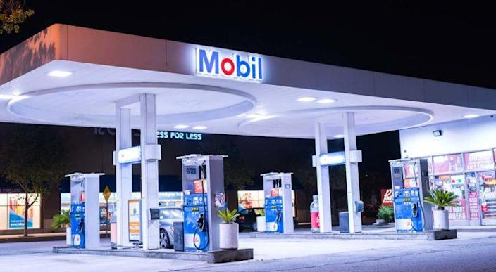 A view of a well-lit Exxon Mobil (XOM) gas station in Pasadena, CA during nighttime.