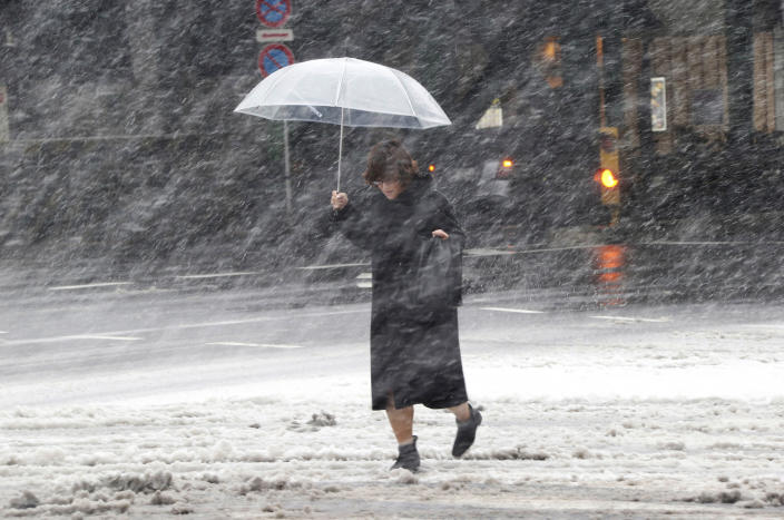 A woman walks against blowing snow in Tokyo, Saturday, Feb. 8, 2014. The Japan Meteorological Agency issued the first heavy snowfall warning for central Tokyo in 13 years. (AP Photo/Koji Sasahara)