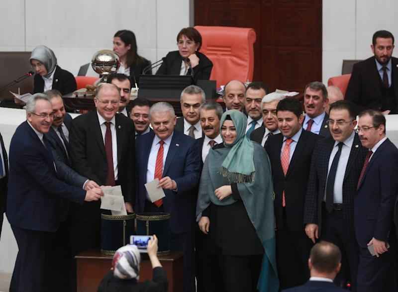 Turkey's Prime Minister Binali Yildirim accompanied by lawmakers votes following a parliament debate on proposed amendments to the country's constitution