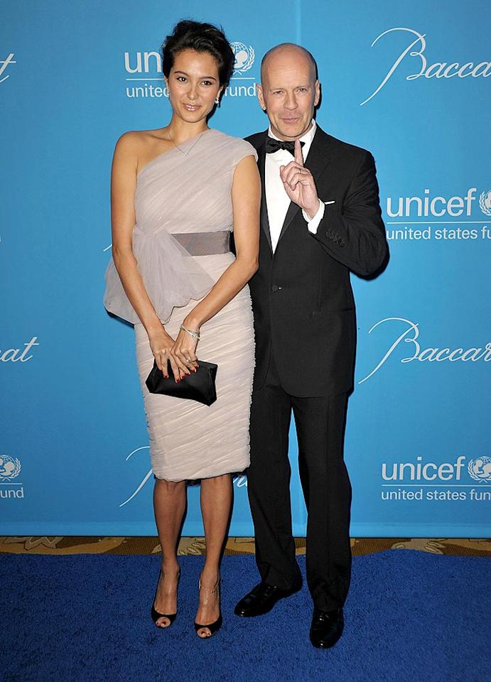 """Bruce Willis and his wife Emma Heming, in a beautiful one-shoulder dress, strike a cheeky pose on their way into the UNICEF event. John Shearer/<a href=""""http://www.wireimage.com"""" target=""""new"""">WireImage.com</a> - December 10, 2009"""