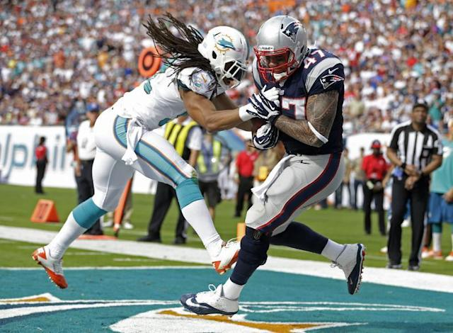 New England Patriots tight end Michael Hoomanawanui (47) grabs a touchdown pass as Miami Dolphins outside linebacker Philip Wheeler (52) defends during the first half of an NFL football game on Sunday, Dec. 15, 2013, in Miami Gardens, Fla. (AP Photo/Lynne Sladky)