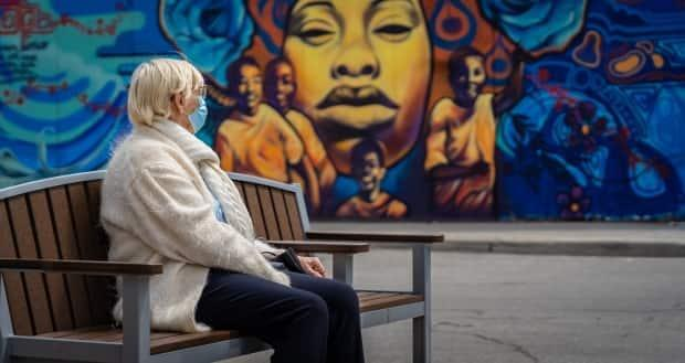 A woman wearing a mask looks at a mural in Ottawa on May 11, 2021. (Brian Morris/CBC - image credit)