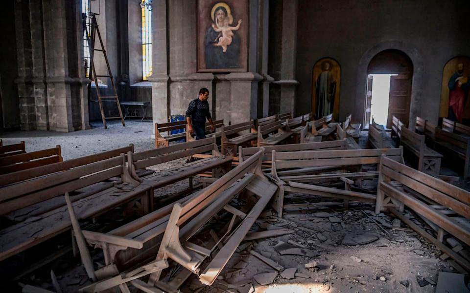 A man walks in rubble on October 8, 2020 inside the Ghazanchetsots (Holy Saviour) Cathedral in the historic city of Shusha, some 15 kilometers from the disputed Nagorno-Karabakh province's capital Stepanakert - AFP