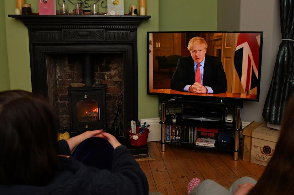 "TOPSHOT - Members of a family listen as Britain's Prime Minister Boris Johnson makes a televised address to the nation from inside 10 Downing Street in London, with the latest instructions to stay at home to help contain the Covid-19 pandemic, from a house in Liverpool, north west England on March 23, 2020. - Britain on Monday ordered a three-week lockdown to tackle the spread of coronavirus, shutting ""non-essential"" shops and services, and banning gatherings of more than two people. ""Stay at home,"" Prime Minister Boris Johnson said in a televised address to the nation, as he unveiled unprecedented peacetime measures after the death toll climbed to 335. (Photo by Paul ELLIS / AFP) (Photo by PAUL ELLIS/AFP via Getty Images)"