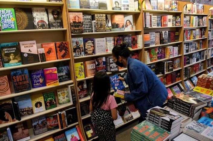 Customers browse books for sale at Eso Won Books in the Leimert Park neighborhood of Los Angeles, California -- the Black-owned small business limits the number of customers in the store