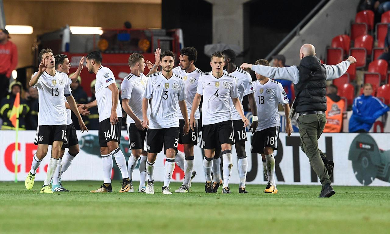Germany's players try to ward off the approaches of a supporter on the pitch after their win against the Czech Republic in Prague.