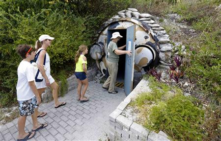 Guests, led by curator Ruth Pelletier (R), enter the cold-war era nuclear fallout shelter constructed for U.S. President John F. Kennedy on Peanut Island near Riviera Beach, Florida November 8, 2013. REUTERS/Joe Skipper
