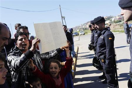 "A Syrian refugees shouts slogans as he holds a placard that reads ""the Syrians are abused by security agents"" outside a refugee centre in Spain's north African enclave Melilla"