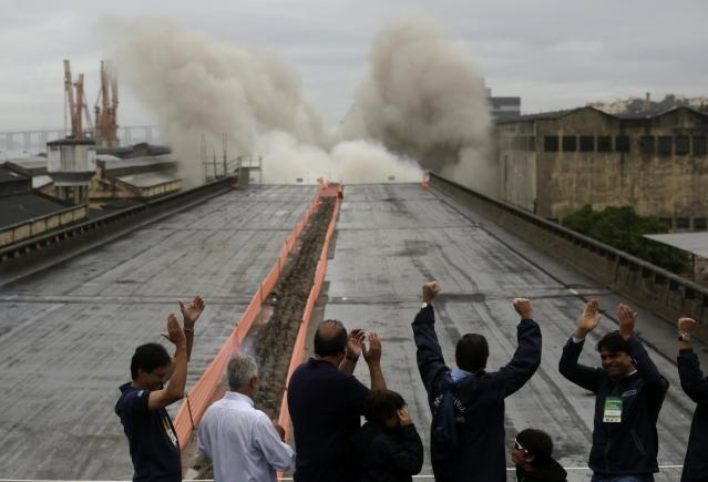 Local authorities celebrate at the moment of Perimetral overpass' demolition explosion, as part of Rio's Porto Maravilha urbanization project, in Rio de Janeiro November 24, 2013. The project, which is supported by the state and federal government of Rio de Janeiro, is for the city's redevelopment ahead of the 2016 Olympic Games. REUTERS/Pilar Olivares (BRAZIL - Tags: POLITICS SPORT OLYMPICS SOCIETY BUSINESS)