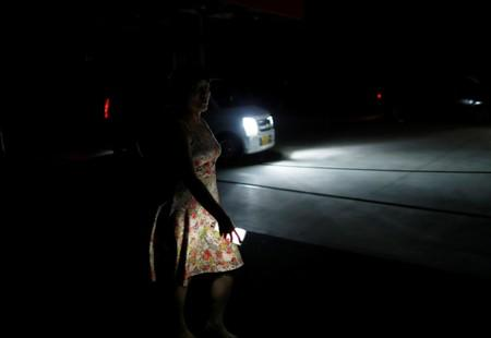 A local resident holding flashlight walks in a blackout caused by Typhoon Faxai in Kisarazu, Japan