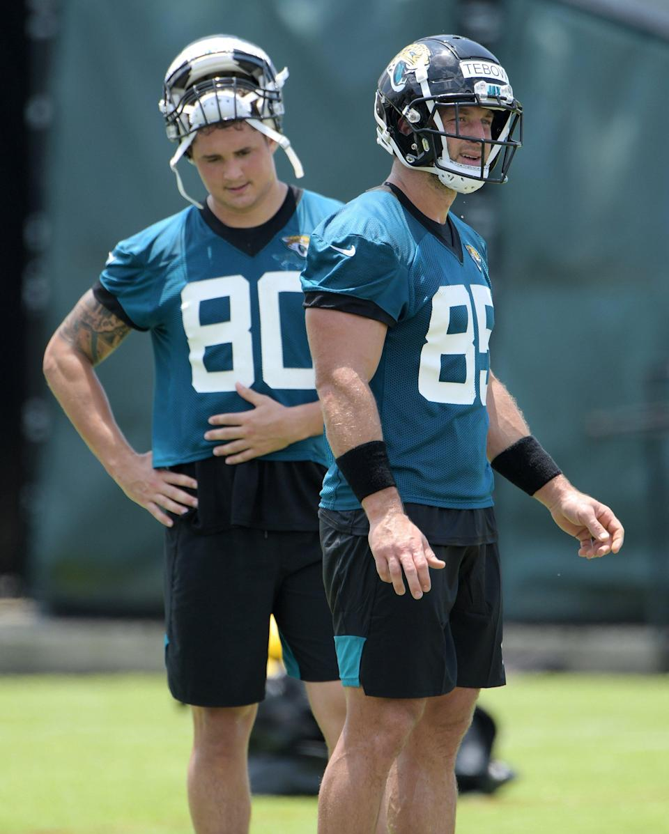 Jaguars (80) TE James O'Shaughnessy and (85) TE Tim Tebow on the field during a break between drills at Thursday's OTA session. (Bob Self/Florida Times-Union)