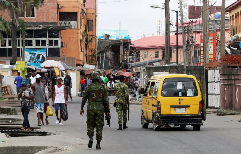 Military personnel walk along a street in Ikeja, in Lagos